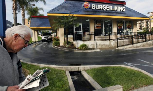FILE - In this Thursday, April 25, 2013, file photo, a pedestrian walks past a Burger King restaurant near downtown Los Angeles. On Friday, April 25, 2014, Burger King reported a higher first-quarter profit as cost-cutting offset weak sales in the U.S. The Miami-based chain said global sales at established locations rose 2 percent, including a 0.1 percent increase in the U.S.(AP Photo/Nick Ut, File)