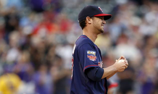 Minnesota Twins starting pitcher Kris Johnson reacts to giving up a two run home run to Colorado Rockies' Drew Stubbs against the Colorado Rockies during the first inning of a baseball game on Friday, July 11, 2014, in Denver. (AP Photo/Jack Dempsey)