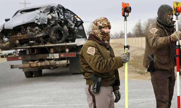 The vehicle driven by a Burns Flat police officer is removed from the crash site as two OHP investigators gather information. Photo by Jim Beckel, The Oklahoman