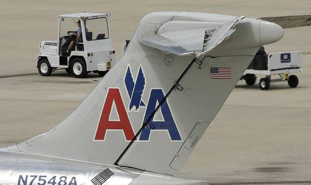 In this May 15, 2014 photo, a ramp worker rolls past an American Airlines McDonnell Douglas MD-82  at the Tampa International Airport in Tampa , Fla. American Airlines reports quarterly financial results on Thursday, July 24, 2014. (AP Photo/Chris O'Meara)