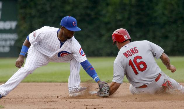 St. Louis Cardinals' Kolten Wong (16) steals second on a throw from Chicago Cubs catcher Welington Castillo to second baseman Arismendy Alcantara, left, during the eighth inning of a baseball game Friday, July 25, 2014, in Chicago. (AP Photo/Charles Rex Arbogast)