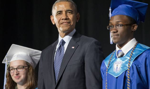 President Barack Obama, flanked by class Valedictorian Naomi Desilets, left, and student body President Reginald Sarpong,stands on stage prior to delivering the commencement address for Worcester Technical High School, Wednesday, June 11, 2014, in Worcester, Mass. (AP Photo/Pablo Martinez Monsivais)