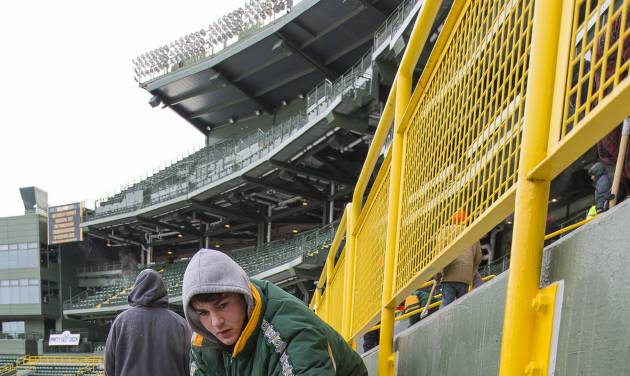 James Diedrick helps clear ice and snow from the seats at Lambeau Field on Friday, Jan. 3, 2014, in Green Bay, Wis., in preparation for Sunday's NFL football wild-card playoff game between the Green Bay Packers and San Francisco 49ers. (AP Photo/Mike Roemer)