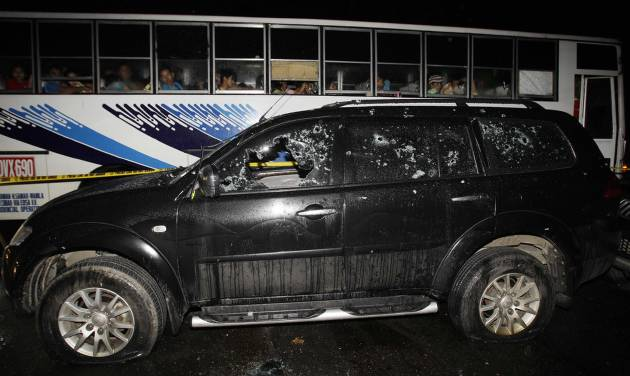 Passengers look at the bullet-riddled vehicle of suspected criminals along a road in the town of Atimonan in Quezon province, about 140 kilometers (100 miles) southeast of Manila, Philippines late Sunday Jan. 6, 2013. Philippine army special forces and police killed 13 suspected criminals in a gunbattle Sunday in the latest violence to erupt in the country in the past week. (AP Photo/Aaron Favila)