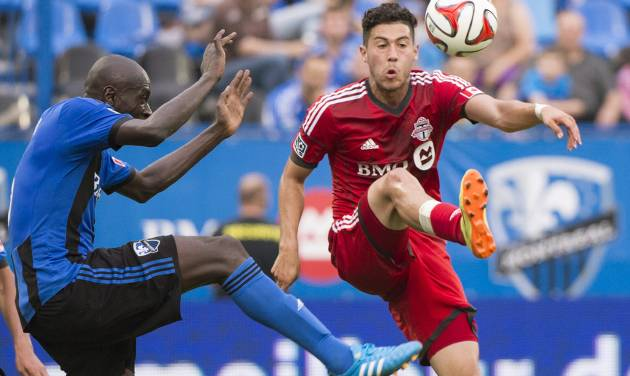 Montreal Impact's Hassoun Camara, left, moves in on Toronto FC's Jonathan Osorio during the second half of a soccer match in Montreal, Saturday, Aug. 2, 2014. (AP Photo/The Canadian Press, Graham Hughes)