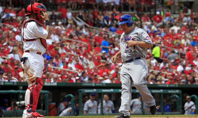 New York Mets' Bartolo Colon, right, scores on a double by Eric Young Jr. as St. Louis Cardinals catcher Yadier Molina, left, watches during the sixth inning of a baseball game Wednesday, June 18, 2014, in St. Louis. (AP Photo/Jeff Roberson)