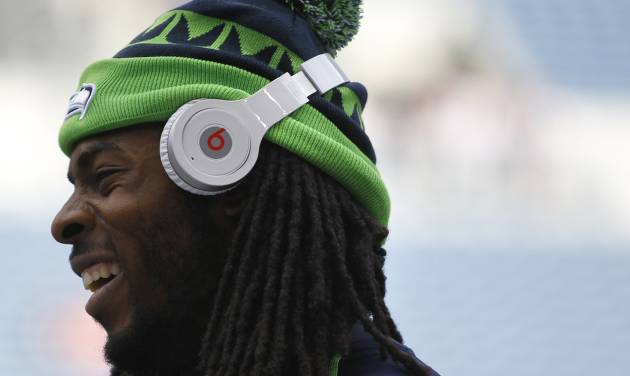 FILE - In this Aug. 17, 2013 photo, Seattle Seahawks' Richard Sherman wears Beats headphones before a preseason NFL football game against the Denver Broncos, in Seattle. Apple's $3 billion purchase of Beats Electronics, by far the company's largest acquisition, is at least in part recognition that Beats founders Dr. Dre and Jimmy Iovine might be able to help Apple incorporate more style and flair into its premium technology gadgets —especially a coming wave of wearable devices. (AP Photo/John Froschauer, File)