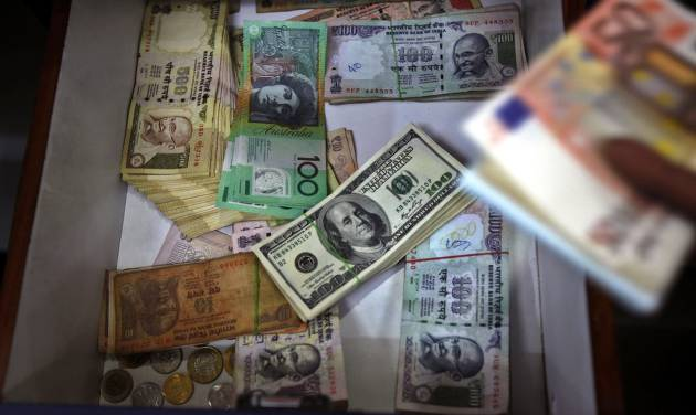 FILE - In this Aug. 22, 2013 file photo, Indian and foreign currency notes lie in a drawer of a foreign currency exchange shop in Bangalore, India. The Treasury Department reports how much foreign buyers adjusted their holdings of U.S. debt in June 2014 on Friday, Aug. 15, 2014. (AP Photo/Aijaz Rahi, File)