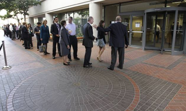 People wait in line to get inside for the Apple and Samsung trial during a lunch break at a federal courthouse in San Jose, Calif., Tuesday, Aug. 21, 2012. After three weeks of listening to technology experts, patent professionals and company executives debate the complicated legal claims of Apple Corp. and Samsung Electronics Co., a jury of nine men and women are set to decide one of the biggest technology disputes in history. (AP Photo/Paul Sakuma)