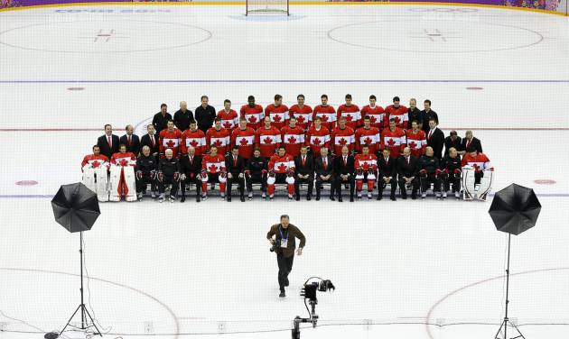 The Canadian men's ice hockey team waits as a photographer runs back to his spot to make a team photo before a training session inside the Bolshoy Ice Dome at the 2014 Winter Olympics, Tuesday, Feb. 11, 2014, in Sochi, Russia. (AP Photo/Julie Jacobson)