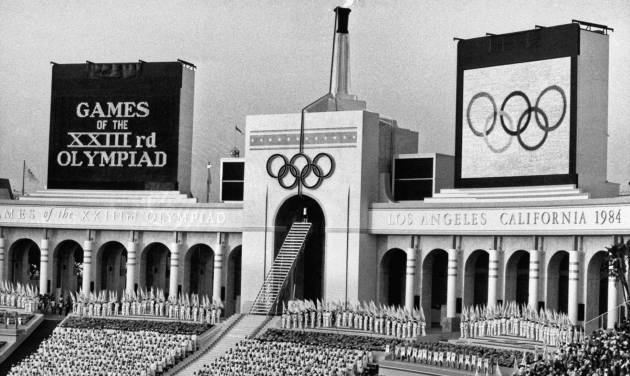 FILE - In this July 28, 1984 file photo, the Olympic flame is flanked by a scoreboard signifying the formal opening of the XXIII Olympiad after it was lit by Rafer Johnson during the opening ceremonies in the Los Angeles Memorial Coliseum. Boston, Los Angeles, San Francisco and Washington are the cities still in the running for a possible U.S. bid to host the 2024 Summer Olympics. (AP Photo/Eric Risberg, File)