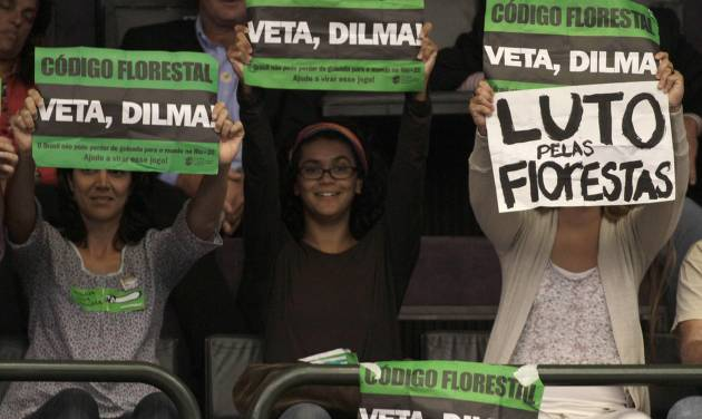 """Environmentalists hold up protest signs that read in Portuguese """"Veto Dilma"""" and """"Mourning for the Forest"""" during a session by Chamber of Deputies who are expected to vote on a new forest law in Brasilia, Brazil, Wednesday, April 25, 2012. Environmentalists say that any changes made to Brazil's benchmark environmental laws will damage the Amazon and other areas. (AP Photo/Eraldo Peres)"""