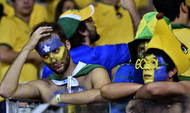 Brazil supporters react after the World Cup semifinal soccer match between Brazil and Germany at the Mineirao Stadium in Belo Horizonte, Brazil, Tuesday, July 8, 2014. Germany won the match 7-1. (AP Photo/Martin Meissner)