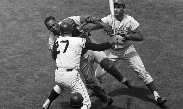 FILE - In this Aug. 22, 1965, file photo, San Francisco Giants pitcher Juan Marichal (27) swings a bat at Los Angeles Dodgers catcher John Roseboro as Dodgers pitcher Sandy Koufax, rear right, tries to break it up in the third inning at Candlestick Park in San Francisco. Violence is part of the game in many sports. But when athletes cross the line it can attract the attention of authorities _ sometimes from within their sport and in other cases from criminal prosecutors. The punishment of four members of the New Orleans Saints for participating a cash-for-hits bounty system targeting opponents is the latest example but not the only one. (AP Photo/Robert H. Houston, File)