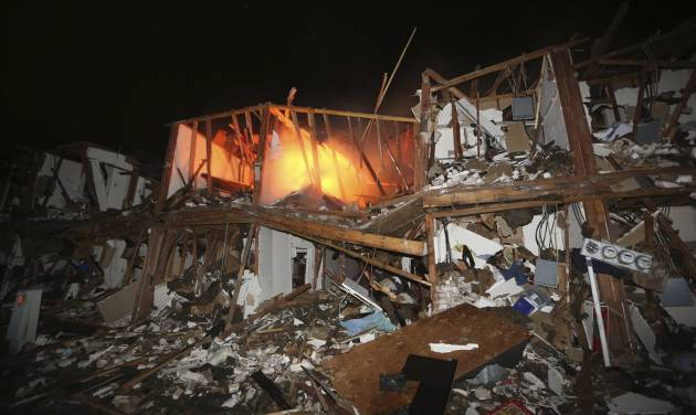 A fire still burns in a apartment complex destroyed near a fertilizer plant that exploded earlier in West, Texas, in this photo made early Thursday morning, April 18, 2013.  (AP Photo/LM Otero)