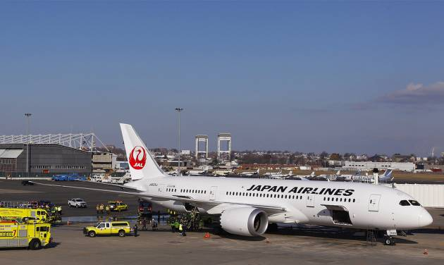 A Japan Airlines Boeing 787 Dreamliner jet aircraft is surrounded by emergency vehicles while parked at a terminal E gate at Logan International Airport in Boston, Monday, Jan. 7, 2013. Boeing has a lot riding on the 787. The long-range jet promises a smoother travel experience and is 20 percent more fuel efficient than older models. After years of delays, Boeing has now delivered 49 of the planes, with almost 800 more on order.  (AP Photo/Stephan Savoia)