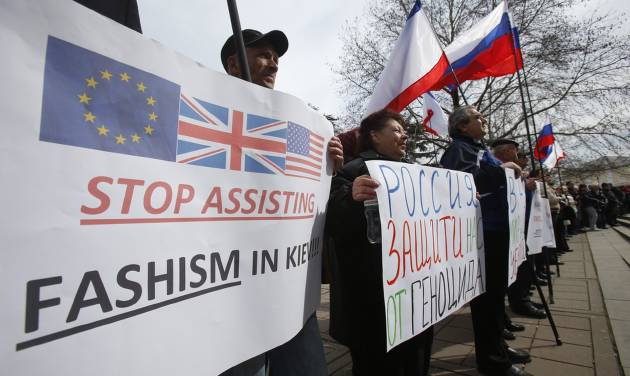 """Pro-Russia demonstrators hold Russian and Crimean flags and posters as they rally in front of the local parliament building in Crimea's capital Simferopol, Ukraine, Thursday March 6, 2014. About 50 people rallied outside the local parliament Thursday morning waving Russian and Crimean flags. Lawmakers in Crimea called a March 16 referendum on whether to break away from Ukraine and join Russia instead, voting unanimously Thursday to declare their preference for doing so. A poster reads """"Russia, Defend us from Genocide."""" (AP Photo/Sergei Grits)"""