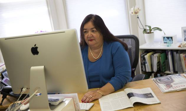 Jane Delgado, president of the National Alliance for Hispanic Health, works in her office in Washington, Monday, March 24, 2014. The nation's largest minority group risks being left behind by President Barack Obama's health care overhaul. Hispanics account for nearly one-third of the nation's uninsured, but all signs indicate that they remain largely on the sidelines as the White House races to meet a goal of 6 million sign-ups with less than a week to enroll. (AP Photo/ Evan Vucci)