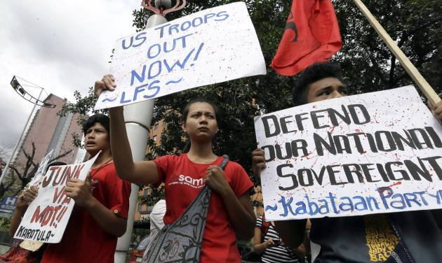 Protesters display placards during a rally at the U.S. Embassy in Manila to protest the recent incident in the Philippines wherein a U.S. Navy minesweeper, the USS Guardian, ran aground off Tubbataha Reef, a World Heritage Site in the Sulu Sea, 640 kilometers (400 miles) southwest of Manila, Philippines Saturday Jan. 19, 2013. The protesters are demanding the abrogation of the Visiting Forces Agreement which allows U.S. troops' presence in the country. (AP Photo/Bullit Marquez)