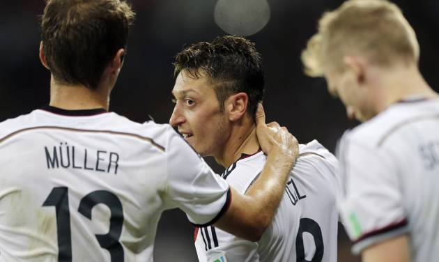 Germany's Mesut Ozil celebrates after scoring his side's second goal in extra time with teammate Thomas Mueller during the World Cup round of 16 soccer match between Germany and Algeria at the Estadio Beira-Rio in Porto Alegre, Brazil, Monday, June 30, 2014. Germany defeated Algeria 2-1 to advance to the quarterfinals.  (AP Photo/Matthias Schrader)