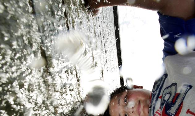 Kevin Sanabria, 10, plays in a small waterfall in Trenton, N.J., Saturday, July, 7, 2012. People were coping as temperatures in the region climbed into the high 90s. (AP Photo/Mel Evans)