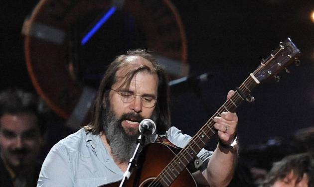 """FILE - In this May 3, 2009 file photo, musician Steve Earle performs at a benefit concert celebrating Pete Seeger's 90th birthday at Madison Square Garden in New York. Earle has released a CD and his debut novel with the same titles, """"I'll Never Get Out of This World Alive."""" (AP Photo/Evan Agostini, file)"""