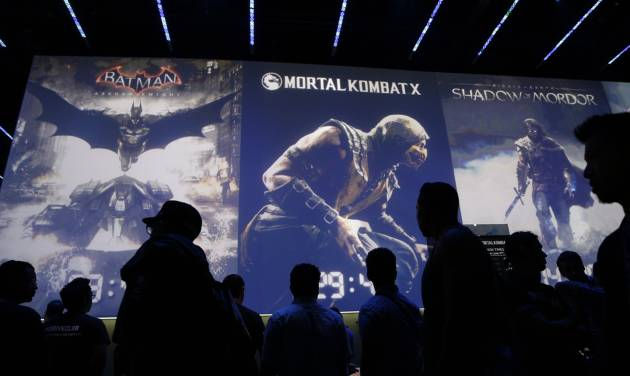 FILE - In this Wednesday, June 11, 2014 file photo, people wait in line for theater presentations for video games including Batman, Mortal Kombat X and Shadow of Mordor at the WB Games booth at the Electronic Entertainment Expo, in Los Angeles. At last week's E3, video game developers hyped upcoming titles featuring assassins, super-soldiers, vigilantes and demon hunters. The lack of female protagonists at the expo highlighted an ongoing issue that continues to haunt the video game industry.  (AP Photo/Jae C. Hong, file)