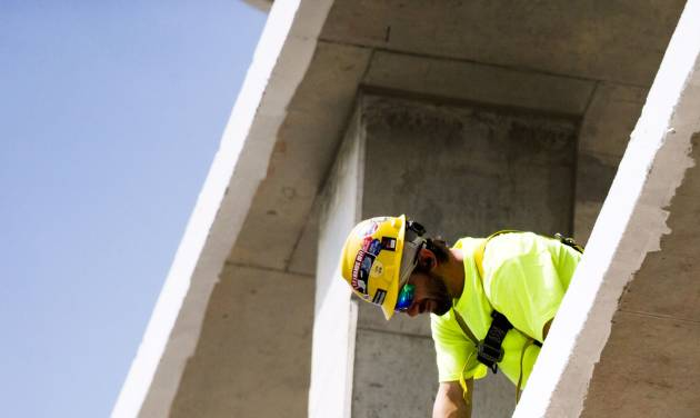 In this July 3, 2014 photo, a construction worker builds housing for students near Drexel University in Philadelphia.  The Commerce Department reports on U.S. construction spending in June on Friday, Aug. 1, 2014. (AP Photo/Matt Rourke)