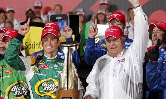 FILE - In this file photo taken May 27, 2012, Kasey Kahne, left, and team owner Rick Hendrick, right, pose with the trophy in Victory Lane after winning the NASCAR Coca-Cola 600 Sprint Cup Series auto race in Concord, N.C. Kahne's contract runs through 2015, about the same time Chase Elliott will be ready for a promotion from the driver development program to the big leagues. Hendrick Motorsports has got to put Elliott somewhere, and there's no guarantee Jeff Gordon is going to smile his way into retirement and hand his seat over to Elliott. (AP Photo/Terry Renna, File)