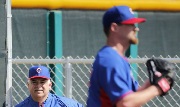 Chicago Cubs manager Rick Renteria, left, watches pitcher Travis Wood throw during the team's first spring training baseball practice, Friday, Feb. 14, 2014, in Mesa, Ariz. (AP Photo/Matt York)