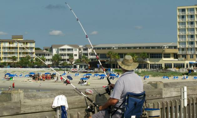 A fisherman tries his luck while beachgoers enjoy the shore at Folly Beach, S.C., in this photograph taken July 1, 2014. In time for the summer tourist season the South Carolina Department of Parks, Recreation and Tourism has upgraded its web site. The department recently spent $500,000 to make the site more interactive. The site helps draw tourists to South Carolina where tourism is an $18 billion industry. (AP Photo/Bruce Smith)