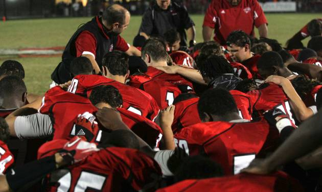 Hartsville head football coach Jeff Calabrese prays with his players just before they take the field to finish the first half of play against Crestwood Friday Oct. 5, 2012 at Kellytown Stadium. Hartsville defense end Ronald Rouse collapsed during the game and later died at a local hospital. The game was suspended at halftime. (AP Photo/Bob Sloan, Florence Morning News)