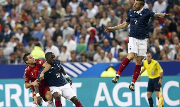France's Mathieu Debuchy, right, jumps for the ball, as France's Moussa Sissoko, center, and Spain's David Azpilicueta look on during their international friendly soccer match at the Stade de France in Saint Denis, outside Paris, Thursday, Sept. 4, 2014. (AP Photo/Christophe Ena)