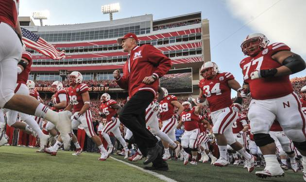 Nebraska's retiring athletic director and former coach Tom Osborne runs onto the field with players prior to an NCAA college football game against Minnesota, in Lincoln, Neb., Saturday, Nov. 17, 2012. Osborne is being honored for his involvement in 500 Nebraska football games. (AP Photo/Dave Weaver)