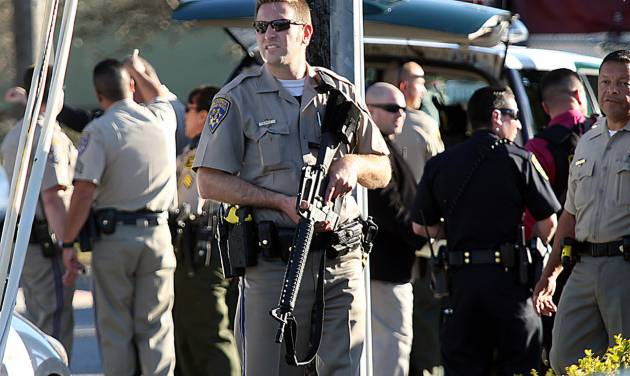 A California Highway Patrol officer carries his rifle near the shooting scene in Santa Cruz, Calif., where two Santa Cruz Police detectives were shot and killed Tuesday, Feb. 26, 2013. The shooting in the community about 60 miles south of San Francisco took place as police were investigating a report of a sexual assault,  Santa Cruz County Sheriff Phil Wowak said. A suspect was shot while police were in pursuit of the shooter, the sheriff said. Authorities said that person also died. (AP Photos/Santa Cruz Sentinel, Dan Coyro)