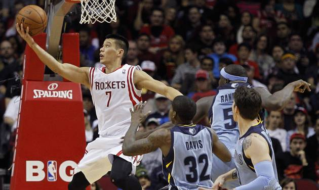 Houston Rockets guard Jeremy Lin (7) drives for a reverse layup past Memphis Grizzlies' Ed Davis (32) and Zach Randolph (50) during the first half of an NBA basketball game Thursday, Dec. 26, 2013, in Houston. (AP Photo/Bob Levey)