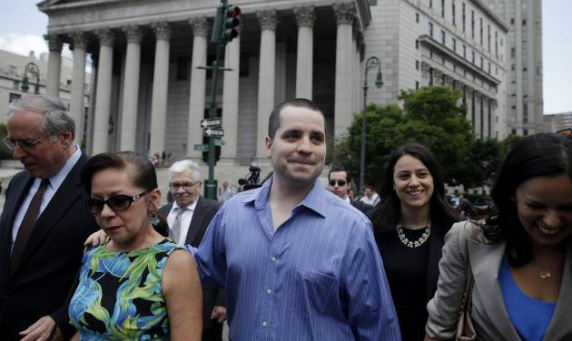 GIlberto Valle, center, leaves Manhattan federal court in New York on Tuesday, July 1, 2014. A federal judge overturned the conviction of the former New York City police officer accused of plotting to kidnap, kill and eat young women. (AP Photo/Seth Weng)