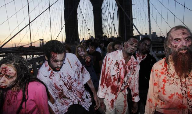 "FILE - Costumed actors, promoting the Halloween premiere of the AMC television series ""The Walking Dead"", shamble along the Brooklyn Bridge while posing for pictures in New York, in this Oct. 26, 2010 file photo. Clemson University English professor Sarah Lauro says people are more interested in zombies when they're dissatisfied with society as a whole. As of last year, Lauro said, zombie walks had been documented in 20 countries. The largest gathering drew more than 4,000 participants at the New Jersey Zombie Walk in Asbury Park, N.J., in October 2010, according to the Guinness World Records. (AP Photo/Seth Wenig, File)"