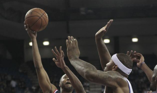 Washington Wizards guard A.J. Price, left, drives to the basket against Sacramento Kings center DeMarcus Cousins during the first quarter of an NBA basketball game in Sacramento, Calif., Wednesday, Jan. 16, 2013. (AP Photo/Rich Pedroncelli)