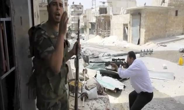 In this image made from video and accessed Saturday, Sept. 1, 2012, a Free Syrian Army fighter calls out to comrades as another fighter fires at Syrian Army positions in Aleppo, Syria. Syrian troops bombarded the northern city of Aleppo Saturday with warplanes and mortar shells as soldiers clashed with rebels in different parts of Syria's largest city, activists said. The Britain-based Syrian Observatory for Human Rights said the clashes were concentrated in several tense neighborhoods where some buildings were damaged and a number of people were wounded. (AP Photo/Robert King via AP video)