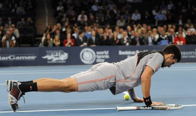Novak Djokovic performs a push up on the court during play against Andy Murray in the BNP Paribas Showdown Tennis Tournament on Monday, March 3, 2014, in New York. Djokovic won 6-3, 7-6. (AP Photo/Kathy Kmonicek)