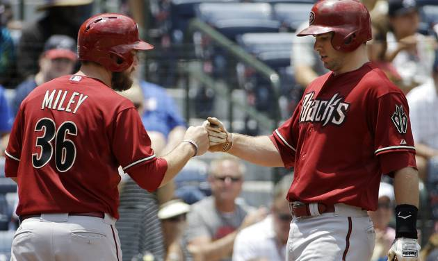 Arizona Diamondbacks' Paul Goldschmidt, right, fist-bumps teammate Wade Miley after hitting a two-run home run to score them in the third inning of a baseball game against the Atlanta Braves, Sunday, July 6, 2014, in Atlanta. (AP Photo/David Goldman)