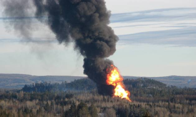 A large fireball rises from the site of a train derailment in New Brunswick, Canada, Friday, Jan. 10, 2014 as officials used a controlled explosion to blast holes in three tanker cars in the hopes of fighting a large fire that continues to burn two and half days after the incident. Canadian National Railway spokesman Jim Feeny says the procedure they used is known as vent and burn, and preliminary indications are that it went according to plan. (AP Photo/The Canadian Press, Kevin Bissett)