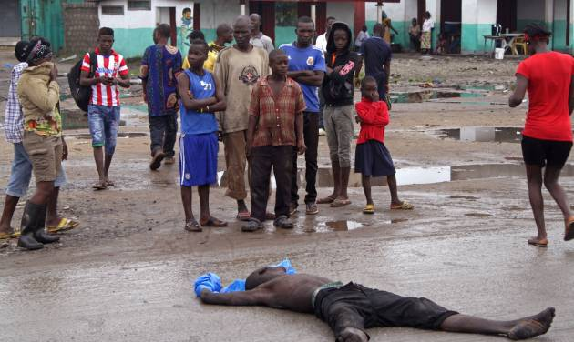 """People gather around a man suspected of dying from the Ebola virus, in one of the main streets on the outskirts of the city center of  Monrovia, Liberia, Tuesday, Aug. 26, 2014. The Ebola virus has the """"upper hand"""" in an outbreak that has killed more than 1,400 people in West Africa, a top American health official has said, but experts have the tools to stop it.(AP Photo/Abbas Dulleh)"""