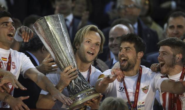 Sevilla's Ivan Rakitic holds the trophy after winningthe Europa League soccer final between Sevilla and Benfica, at the Turin Juventus stadium in Turin, Italy, Wednesday, May 14, 2014. (AP Photo/Andrew Medichini)