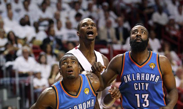 Miami Heat's Chris Bosh, center, fights for position under the basket against Oklahoma City Thunder's Serge Ibaka (9) and James Harden (13) during the third quarter of Game 3 in the NBA Finals basketball series, Sunday, June 17, 2012, in Miami. The Heat won 91-85. (AP Photo/El Nuevo Herald, David Santiago)  MAGS OUT ORG XMIT: FLMEH308