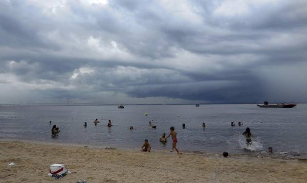 People swim in the Rio Negro in Manaus, Brasilia, Monday, June 16, 2014 despite  staying in the water despite downpours.       (AP Photo/Chris Lehourites)