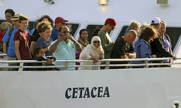 Passengers stand on deck of the whale watch boat Cetacea as it docks Tuesday morning, July 29, 2014 at Long Wharf in Boston. The boat snagged a lobster trap rope during a whale watching excursion about 15 miles off the coast of Massachusetts late Monday, and had to spend a night at sea before divers freed it Tuesday morning. Two Coast Guard cutters remained with the vessel during the night. No injuries were reported to any of the 157 passengers or six crew members. (AP Photo/Boston Herald, Mark Garfinkel)