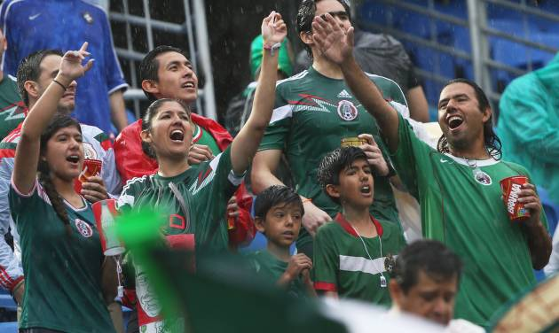 Mexican supporters shout in the rain before the start of the group A World Cup soccer match between Mexico and Cameroon in the Arena das Dunas in Natal, Brazil, Friday, June 13, 2014.  (AP Photo/Sergei Grits)