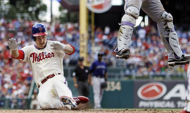 Philadelphia Phillies' Chase Utley, left, scores past Colorado Rockies catcher Wilin Rosario on a two-run double by Ryan Howard in the third inning of the first game of a baseball doubleheader, Sunday, Sept. 9, 2012, in Philadelphia. (AP Photo/Matt Slocum)